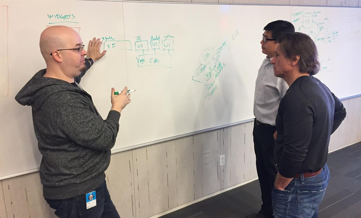 Photo of Nick Landry, Tim Vasko, and Peter Eng whiteboarding during hackfest