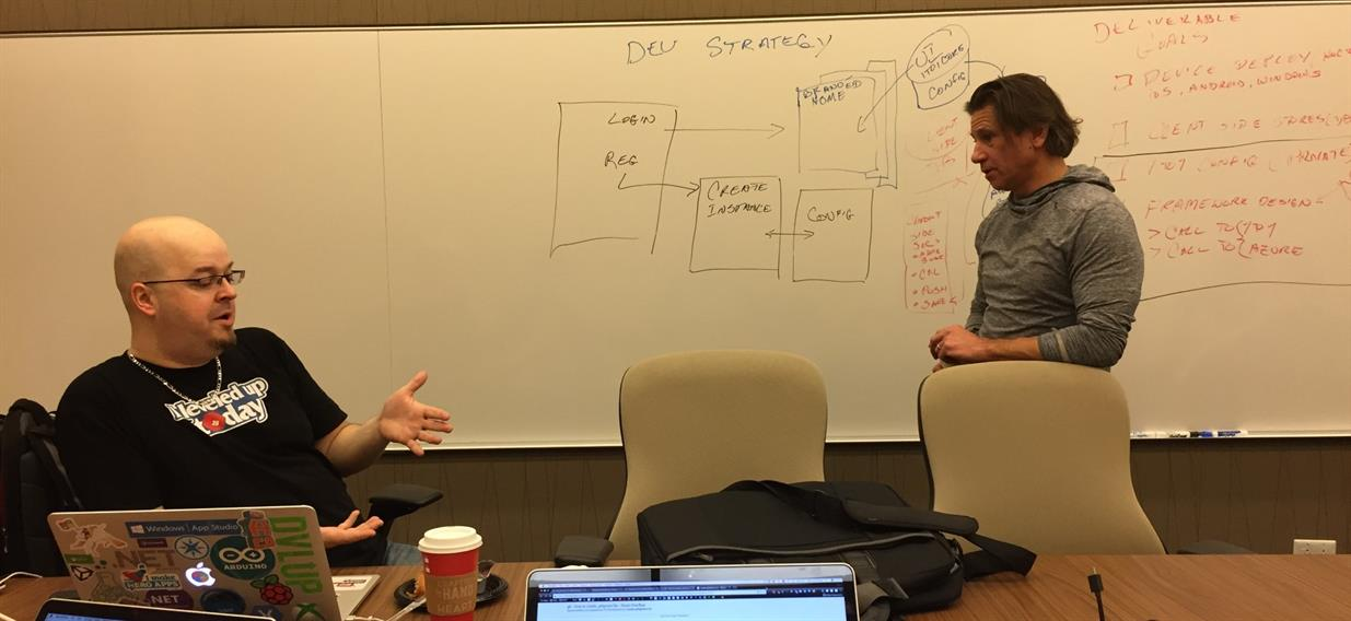 Photo of Nick Landry and Tim Vasko discussing dev strategy during hackfest