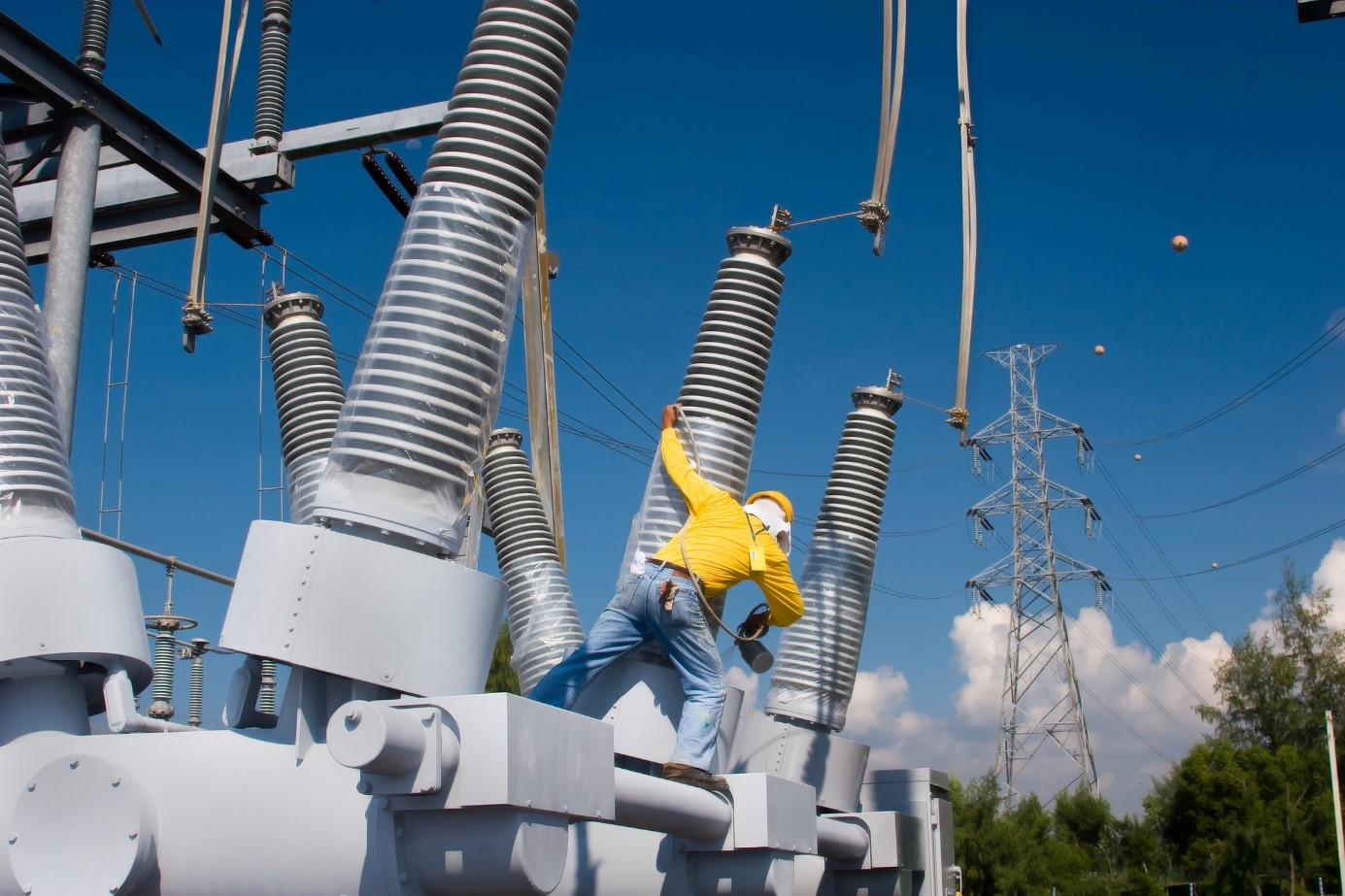 Photo of field engineer working atop substation transformer